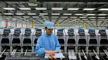 A Celestica employee works on a production line at the Celestica Technology Co. Ltd, a Canada-based electronics company, in China's southern city, Dongguan, Wednesday, July 29, 2009. (Vincent Yu/AP Photo)