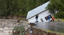 People look on as a house comes off its foundation in Two Mile just outside of Sicamous, B.C. on Monday, June 25, 2012. (JONATHAN HAYWARD/THE CANADIAN PRESS)