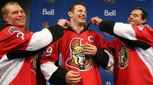 Ottawa Senators' Jason Spezza (centre) has his captain's team jersey adjusted by assistant captains Chris Neil (left) and Chris Phillips (right) after he was named the team's captain in Ottawa, Saturday Sept. 14, 2013. (FRED CHARTRAND/THE CANADIAN PRESS)