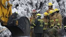 Emergency workers look on while digging through the remains of the senior residence Residence du Havre in L'Isle Verte,Que., on Jan. 25 2014. (Mathieu Belanger/Reuters)