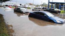 Flooded vehicles sit in water following flash flooding in Kamloops, B.C., on July 23, 2014. (Andrea Klassen/The Canadian Press/Kamloops This Week)