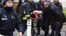 Firefighters carry a victim on a stretcher at the scene after a shooting at the Paris offices of Charlie Hebdo, a satirical newspaper, on Wednesday. (JACKY NAEGELEN/Reuters)