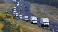 A convoy of white trucks with humanitarian aid moves from Voronezh towards Rostov-on-Don, Russia, early Thursday, Aug. 14, 2014. (Pavel Golovkin/AP)