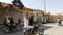 A resident of Tabqa city touring the streets on a motorcycle waves an Islamist flag in celebration after Islamic State militants took over Tabqa air base, in nearby Raqqa city August 24, 2014. (STRINGER/REUTERS)