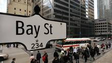 The Bay Street sign is pictured in the heart of the financial district as people walk by in Toronto (MARK BLINCH/REUTERS)