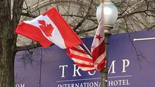 Canadian and American flags fly on Washington's Pennsylvania Avenue in front of a Trump International Hotel sign on Monday, March 7, 2016. (Alexander Panetta/THE CANADIAN PRESS)
