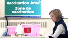 Registered practical nurse Kristen Zaine sits at a vaccine station at the Richelieu-Vanier Community Centre in Ottawa on Sunday, Oct. 25. (Pawel Dwulit/Pawel Dwulit/The Canadian Press)