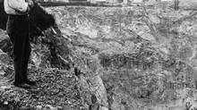 Asbestos mine, Thetford Mines, Quebec, Canada. August 13, 1926. Photo a man standing at the edge of a cliff looking down into the asbestos mine. Credit: Library of Congress