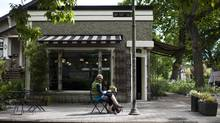 A customer sits outside the Mighty Oak neighbourhood grocery store in Vancouver, British Columbia, Thursday, May 23, 2013. (Rafal Gerszak for The Globe and Mail)