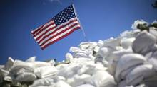 A U.S. flag sits atop a pile of sand bags (© ERIC THAYER / Reuters/Eric Thayer/Reuters)