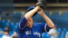 Toronto Blue Jays starting pitcher Mark Buehrle wipes his brow after giving up two runs to the Tampa Bay Rays during the seventh inning of their AL baseball game action in Toronto on Saturday, August 23, 2014. (Fred Thornhill/THE CANADIAN PRESS)