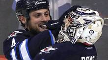 Winnipeg Jets goalie Ondrej Pavelec (31) and Zach Bogosian (4) celebrate a win over the Pittsburgh Penguins at the MTS Centre in Winnipeg, Monday, October 17, 2011. The new Jets claimed their first win 2-1. THE CANADIAN PRESS/John Woods (John Woods/CP)