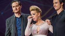 In this photo provided by TED 2014 Conference, dancer Adrianne Haslet-Davis, center, wipes away a tear while standing on stage with MIT professor Hugh Herr, left, and dancer Christian Lightner, at the 2014 TED Conference, Wednesday, March 19, 2014, in Vancouver. Haslet-Davis took to the stage to perform for the first time since losing part of her left leg in the 2013 Boston Marathon bombing. Herr designed the bionic leg specifically for dancing after visiting Haslet-Davis in the hospital. (James Duncan Davidson/AP)