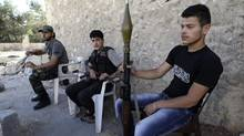 Free Syrian Army fighters carry their weapons as they sit near the front line in Aleppo on June 21, 2013. (MUZAFFAR SALMAN/REUTERS)