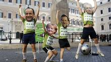 Demonstrators wearing masks depicting French President François Hollande, left, German Chancellor Angela Merkel, Spanish Prime Minister Mariano Rajoy and Italian Prime Minister Mario Monti simulate playing a soccer match to protest against the euro zone debt crisis in Rome, June 22, 2012. (Remo Casilli/Reuters)