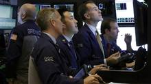 In this Monday, Nov. 18, 2013, file photo, traders work in a booth on the floor of the New York Stock Exchange. (Richard Drew/AP)