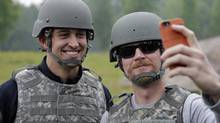 In this July 23, 2014, photo, NASCAR driver Dale Earnhardt Jr. takes a selfie of himself and IndyCar driver Graham Rahal during a visit with Indiana National Guard troops at Camp Atterbury in Edinburgh, Ind. The National Guard is ending its sponsorship of both NASCAR's most popular driver and one of the most recognizable names in IndyCar. It's not clear when the guard is leaving motorsports. It said in a Wednesday, Aug. 6, 2014, statement on its web site that its contracts to sponsor Dale Earnhardt Jr. in NASCAR and Graham Rahal in IndyCar run through the end of the year. (Darron Cummings/AP)