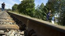 A man walks down the railway tracks in Lac-Mégantic, Que., on July 12, 2013. (PETER POWER/THE GLOBE AND MAIL)