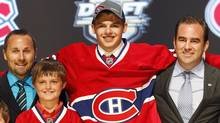 Alex Galchenyuk, centre, smiles with officials from the Montreal Canadiens after being chosen third overall in the first round of the NHL hockey draft on Friday, June 22, 2012, in Pittsburgh. (Associated Press)