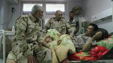 Military personnel visit a Shia volunteer with the Iraqi Army, lying in a hospital bed after being wounded in clashes with militants of the Islamic state, formerly known as the Islamic state in Iraqi and the Levant, in Basra August 6, 2014. (Reuters)