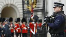 An armed police officer keeps guard as British soldiers march out of Buckingham Palace after the changing of the guard ceremony in London on May 23, 2013. (Kirsty Wigglesworth/Associated Press)
