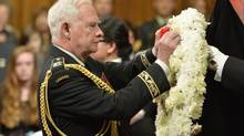 The Governor-General David Johnston places a flower on a wreath at Friday's ceremony. (ADRIAN WYLD/THE CANADIAN PRESS)