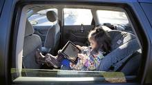 Olivia Lehmann, 3, sits in the back of her mom's car sitting in a child car seat playing on her fathers iPad in Richmond, B.C. November 3, 2010. (John Lehmann/The Globe and Mail/John Lehmann/The Globe and Mail)