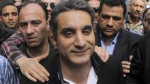 "A bodyguard secures popular Egyptian television satirist Bassem Youssef, who has come to be known as Egypt's Jon Stewart, as he enters Egypt's state prosecutors office to face accusations of insulting Islam and the country's Islamist leader in Cairo, Egypt, Sunday, March 31, 2013. Youssef was later released on bail and would have faced up to three years in prison if found guilty. The Capital Broadcast Centre television channel said only that Youssef's program, called The Program, recorded on Oct. 31, 2013, ""violated editorial policy"" and thereby broke his contract with the channel. (Amr Nabil/AP)"