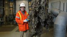 "Barry Orr lifts a giant mass of material, primarily ""flushable"" wipes in London, Ont. on Nov. 15, 2013. (Dave Chidley/THE CANADIAN PRESS)"