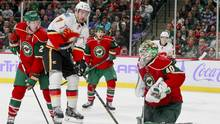 Calgary Flames defenseman TJ Brodie (7) goes airborne as Minnesota Wild goalie Devan Dubnyk (40) makes a save during the second period of an NHL hockey game, Tuesday, Nov. 15, 2016, in St. Paul, Minn. Wild defenseman Ryan Suter (20) is at left. Calgary won 1-0. (Paul Battaglia/The Associated Press)
