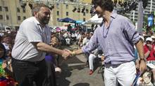 Liberal Party of Canada Leader Justin Trudeau, right, shakes hands with NDP Leader Thomas Mulcair as they attend an outdoor church service before the gay pride parade in Toronto in June, 2013. Each leader has taken a different approach in responding to Quebec's proposed religious-symbols ban. (MARK BLINCH/REUTERS)