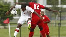 Canada's Julian DeGuzman (6) and Trinidad and Tobago's Richard Roy (12) battle for the ball during the first half of a friendly soccer game in Lauderdale Hill, Fla., Wednesday, Aug. 15, 2012. (AP)