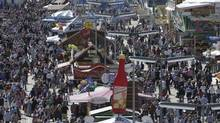 """Visitors enjoy a sunny day at the famous Bavarian """"Oktoberfest"""" beer festival in Munich, southern Germany, Tuesday, Sept. 25, 2012. The world's largest beer festival, to be held from Sept. 22 to Oct. 7, 2012 will see some million visitors. \ (Matthias Schrader/AP)"""