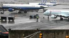 United and Air Canada jets, seen through rain and fog, sit on the tarmac as taxis wait in traffic at John F. Kennedy International Airport in New York. (DANIEL BARRY/DANIEL BARRY/BLOOMBERG NEWS)