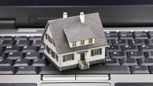 Miniature model home sitting on a laptop keyboard. (Amy Walters/iStockphoto)