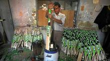 A worker adjusts the grip on the handle of a cricket bat at a factory in Meerut, India. (PARIVARTAN SHARMA/REUTERS/PARIVARTAN SHARMA/REUTERS)