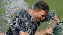Chicago Cubs vice president of baseball operations Theo Epstein is dunked with a bucket of water as part of the ice bucket challenge in awareness for ALS research after the game between the Cubs and Milwaukee Brewers at Wrigley Field. (Jerry Lai/USA Today Sports)