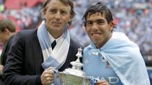 Manchester City's manager Roberto Mancini (L) and Carlos Tevez hold the trophy after defeating Stoke City in their FA Cup final soccer match at Wembley Stadium, in London May 14, 2011. (EDDIE KEOGH/Reuters)