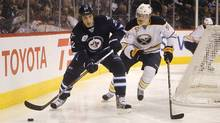 Winnipeg Jets' Chris Thorburn and Buffalo Sabres' Tyler Myers battle for the puck behind the Buffalo net during the second period. (Trevor Hagan/Trevor Hagan/The Canadian Press)