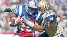 Montreal Alouettes' Victor Anderson (20) is tackled by Winnipeg Blue Bombers' Marcellus Bowman (38) during first half CFL football action in Montreal, Monday, October 8, 2012. (Graham Hughes/THE CANADIAN PRESS)