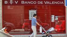 A man pushes a pram past a Banco de Valencia bank branch in Madrid June 25, 2012. Spain formally requested on Monday European aid of up to 100 billion euros for its banks but did not specify how much money it will seek to recapitalize ailing lenders. (Andrea Comas/REUTERS)