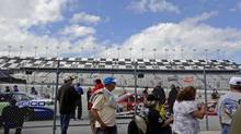 Fans look on as NASCAR Sprint Cup Series crew members wait to enter a routine vehicle inspection station for the Daytona 500 at Daytona International Speedway in Daytona Beach, Florida, February 15, 2013. (BRIAN BLANCO/REUTERS)