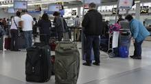 Air Canada passengers line-up at the baggage check-in counter at Pearson International Airport in Toronto (Mike Cassese/Reuters)