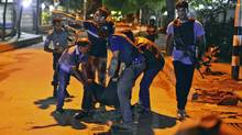 People help an injured person after a group of gunmen attacked a restaurant in the Bangladeshi capital Dhaka. Officials believe Tamim Chowdhury was the architect behind the attack that killed 24 in the name of the Islamic State movement. (Associated Press)