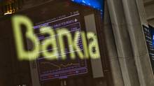 The stock exchange's main display in Madrid is reflected on a Bankia sign. Shares of Spain's bailed-out bank plunged 13 per cent on Thursday after officials with the nation's bank bailout fund revealed the nationalized institution had a negative value of $5.6 billion. (Daniel Ochoa de Olza/AP)