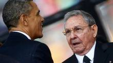 U.S. President Barack Obama (L) greets Cuba's President Raul Castro before giving his speech at the memorial service for late South African President Nelson Mandela in Johannesburg in this December 10, 2013 file photo. The United States and Cuba agreed on December 17, 2014 to restore diplomatic ties that Washington severed more than 50 years ago, and Obama called for an end to the long economic embargo against its old Cold War enemy. After 18 months of secret talks, Obama and Castro agreed in a phone call on December 16 on a breakthrough prisoner exchange, the opening of embassies in each other's countries, and an easing of some restrictions on commerce. (KAI PFAFFENBACH/REUTERS)