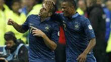 France's Franck Ribery (L) celebrates with teammate Patrice Evra after scoring the third goal for the team during their World Cup qualifying soccer match against Belarus in Saint-Denis, near Paris, September 11, 2012. (BENOIT TESSIER/REUTERS)