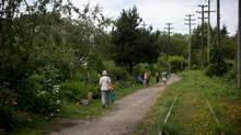 People walk past a community garden along the CP Rail tracks near West 6th Ave. and Cypress Street in Vancouver, B.C., on Thursday July 3, 2014. (DARRYL DYCK For The Globe and Mail)