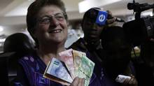 South Africa's reserve bank governor Gill Marcus displays new bank notes bearing the image of former president Nelson Mandela, in Pretoria Nov. 6, 2012. Ms. Marcus is one of only 12 central bank heads who are women. (Denis Farrell/AP)