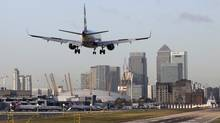 A British Airways aircraft lands at City Airport against a backdrop of the Canary Wharf financial district in London on Tuesday, Dec. 4, 2012. (Chris Ratcliffe/Bloomberg)